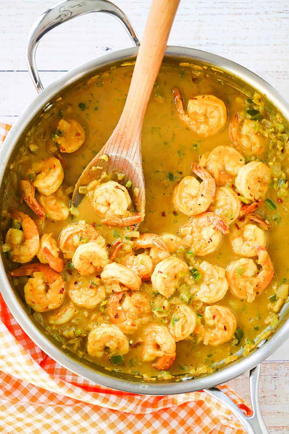 A large stainless steel skillet filled with shrimp curry in a sauce with a wooden spoon insert into the middle of it.