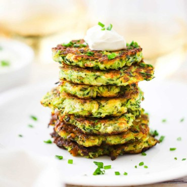 A stack of zucchini fritters on a white dinner plate topped with a dollop of sour cream and snipped chives sprinkled all over.