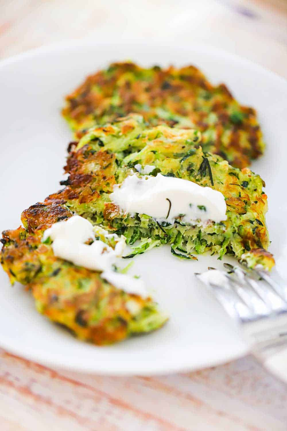 A zucchini fritter that has been split open with a fork and topped with a dollop of sour cream on a white dinner plate.