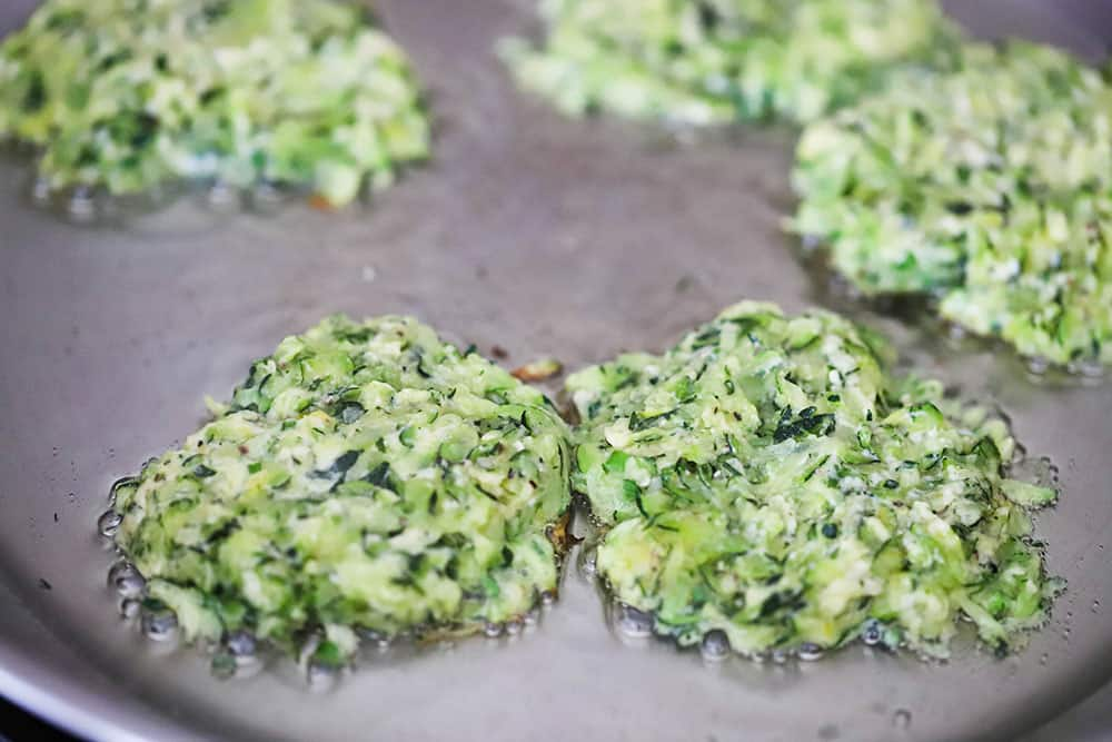 Zucchini fritters being fried in olive oil in a stainless steel skillet.