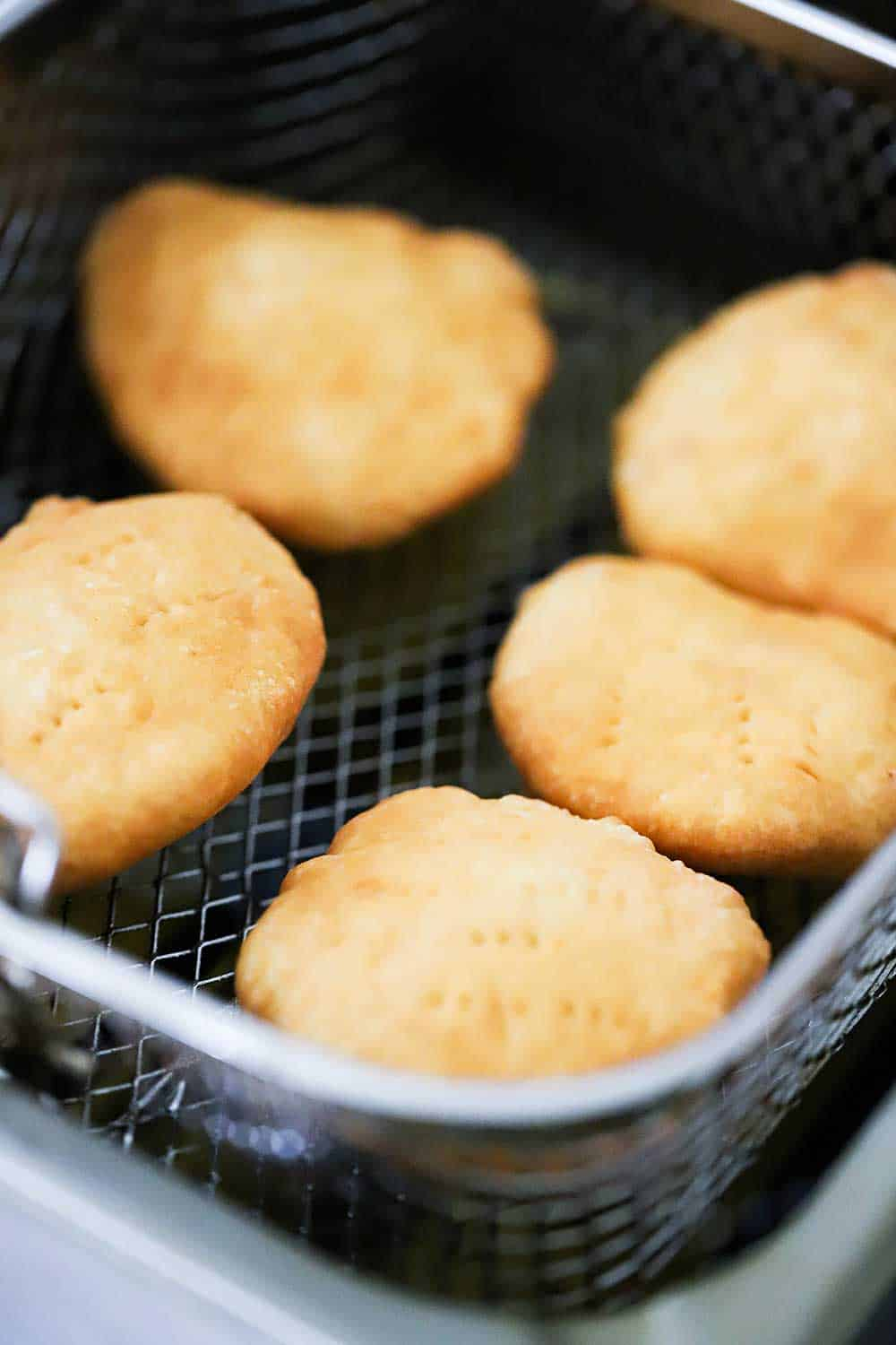 Golden brown Johnny cakes in a basket sitting over a deep fryer.