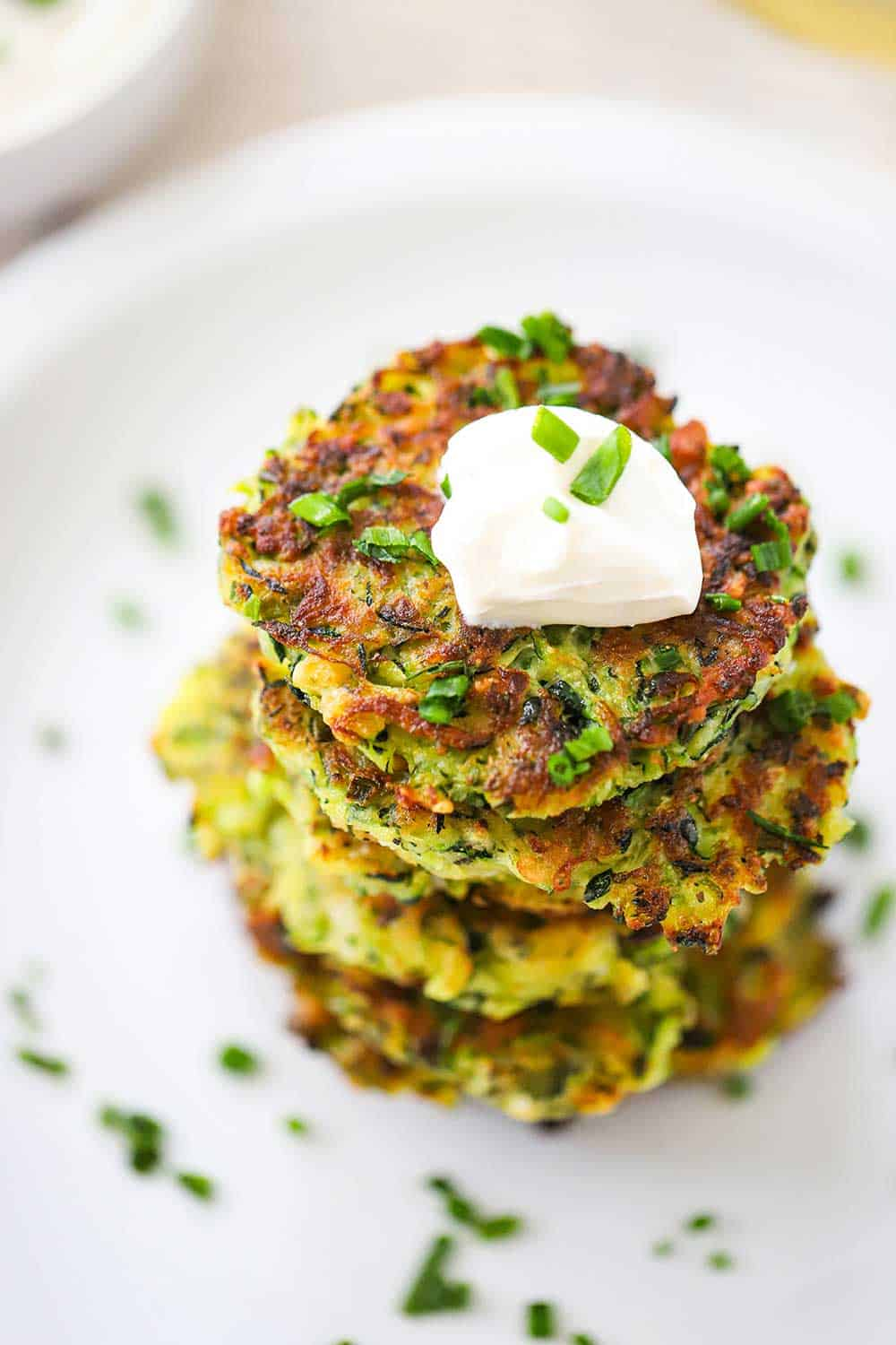 A stack of zucchini fritters on a white plate with a dollop of sour cream on the top fritter and sprinkled with snipped chives.