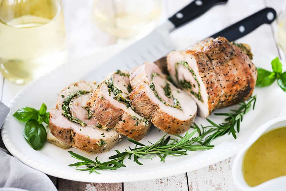 An herb-stuffed pork loin that has been cut into several slices on an oval platter with fresh herbs next to it.