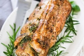 An herb-stuffed pork loin roast sitting on an oval platter with a large knife and fresh herbs nestled around it.