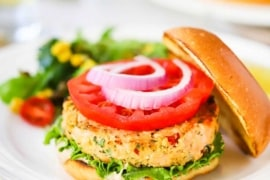 A fully cooked salmon burger on a hamburger bun, garnished with lettuce, tomato, and red onion all sitting on a white plate.