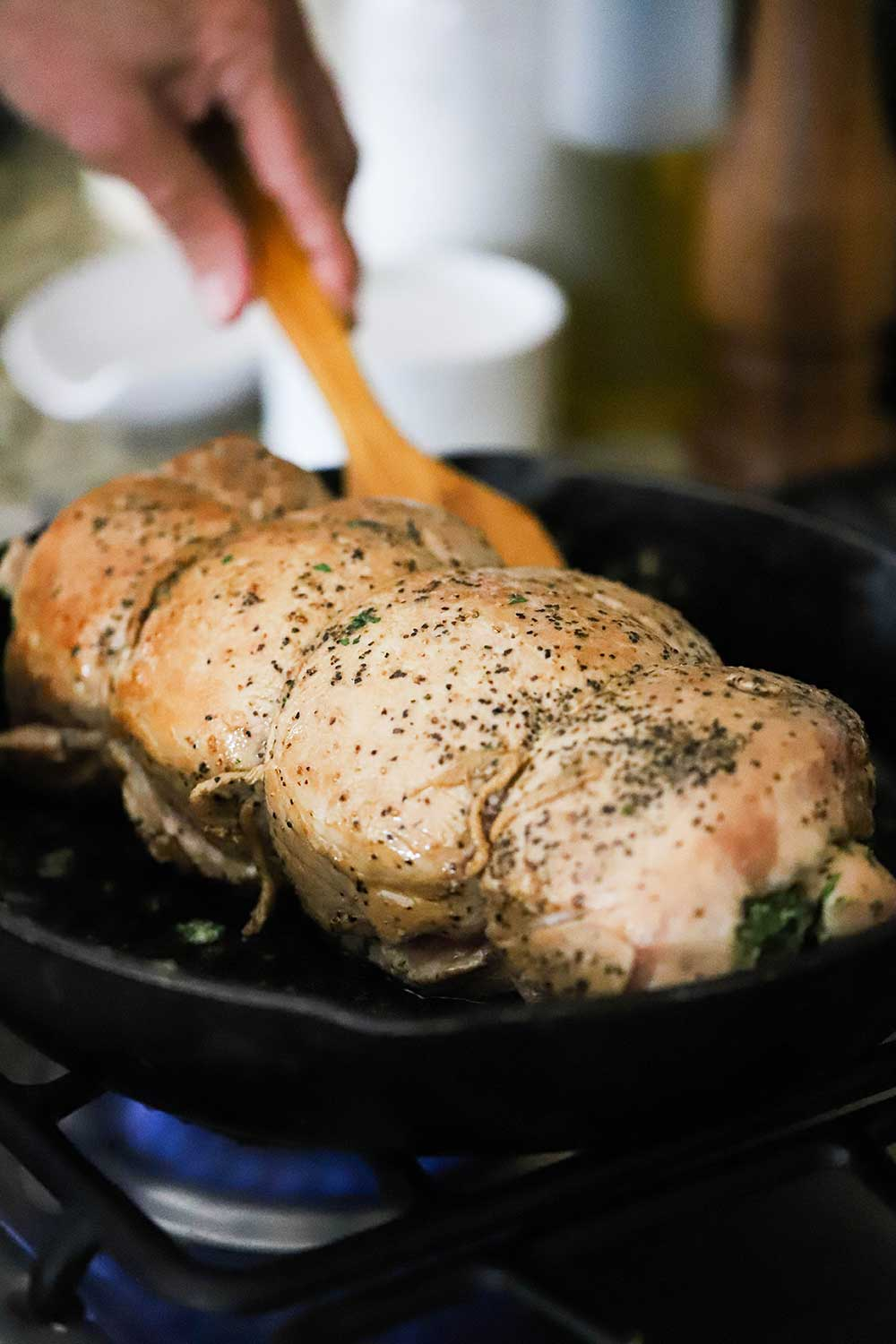 A pork loin that is rolled and tied with twine being seared in a cast-iron skillet.