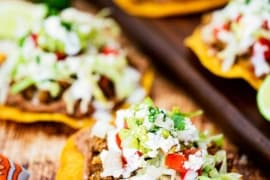 A tostada on a wooden background topped with refried beans, taco meat, lettuce, tomatoes, and Mexican cream, surround by other assembled tostadas.