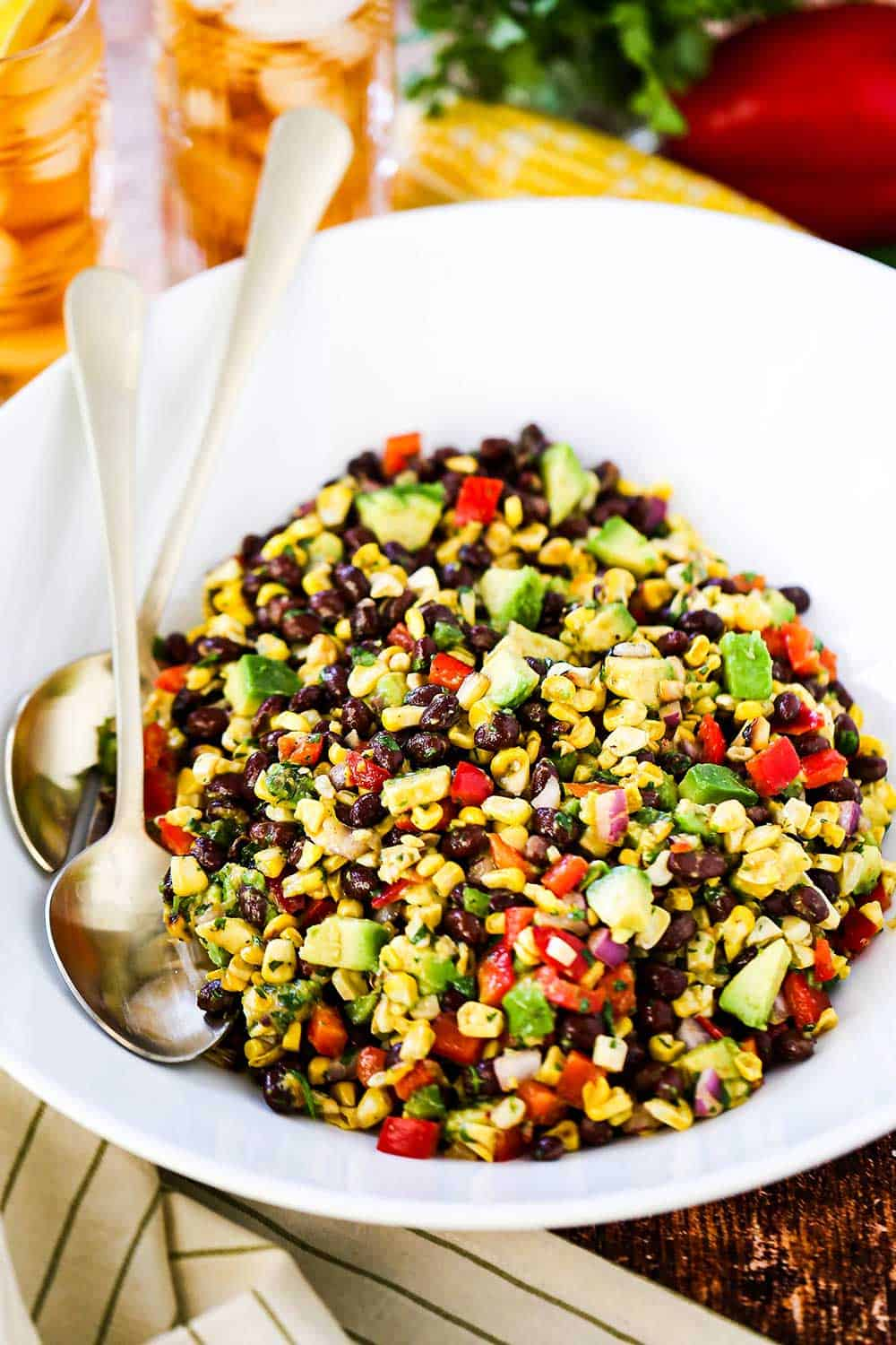 A large white serving bowl filled with black bean and corn salad with two gold serving spoons tucked in beside the salad.