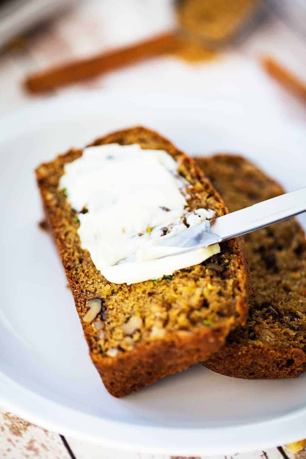 Two slices of zucchini bread being smeared with softened butter all sitting on a white plate.