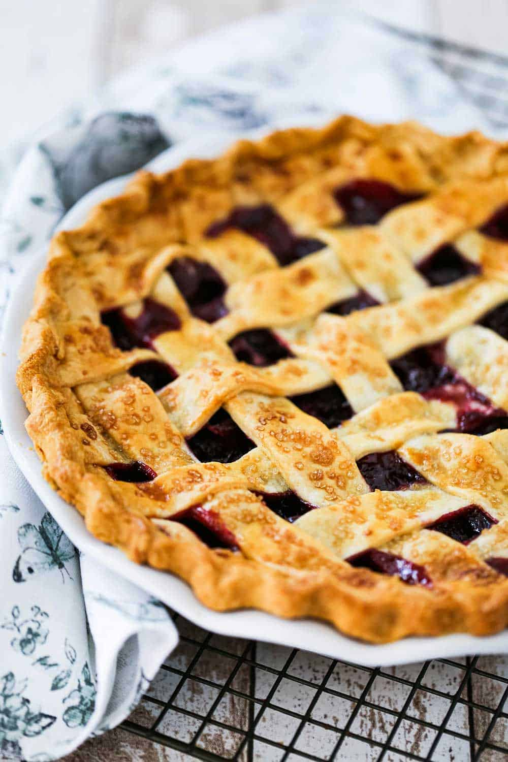 A white pie dish filled with a fully baked cherry pie with a lattice crust topping on it.