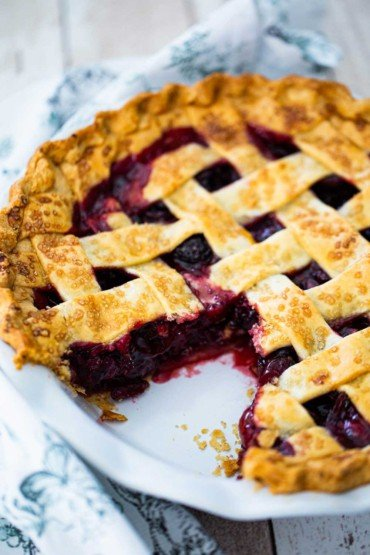 A white pie dish filled with a fully baked cherry pie with a slice missing.