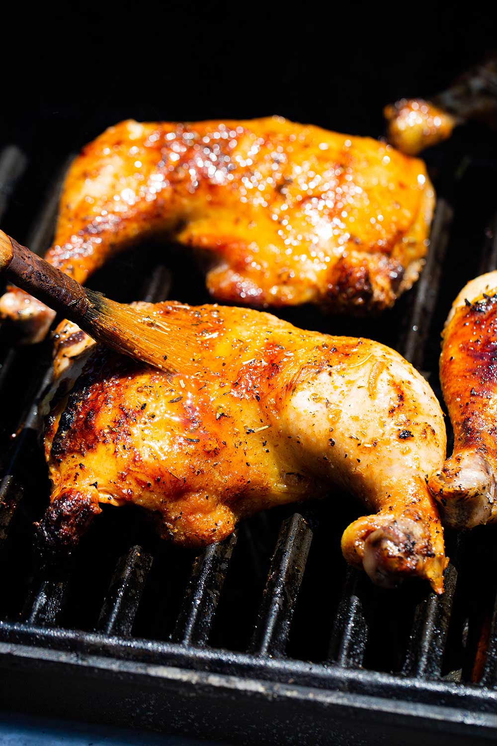 A chicken leg quarter on a gas grill being basted with a brush.