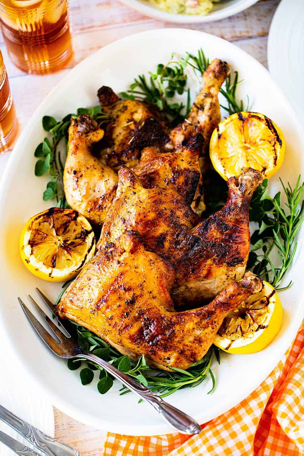 Three grilled chicken leg quarters on an oval platter surround by grilled lemon halves and fresh herbs.