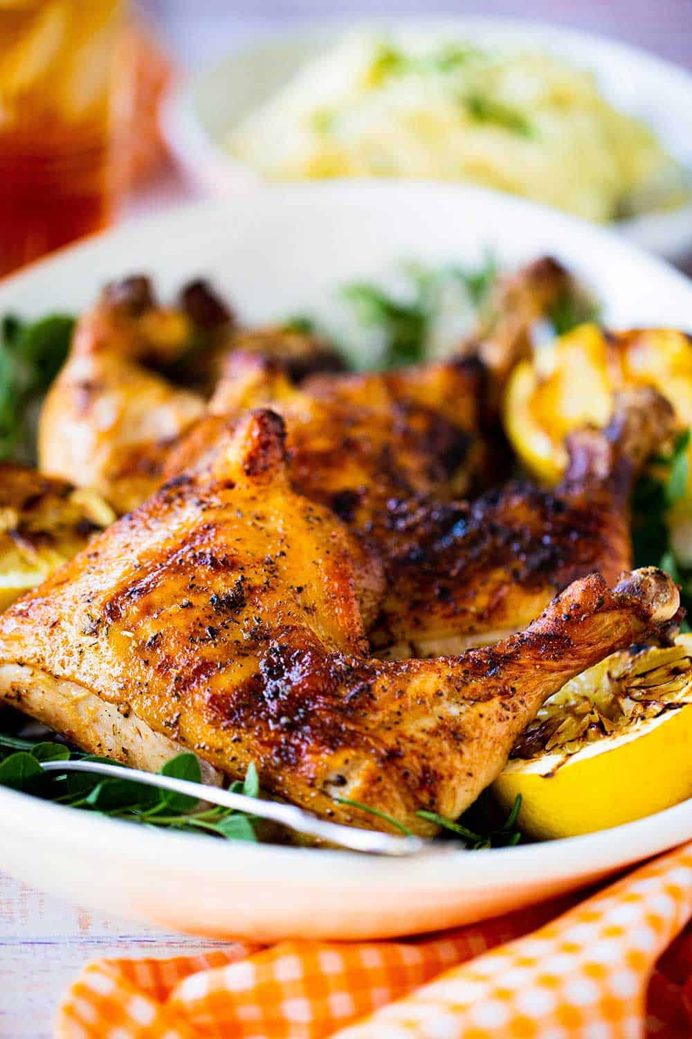 A grilled chicken leg quarter sitting on a platter next to grilled lemons and fresh herbs.