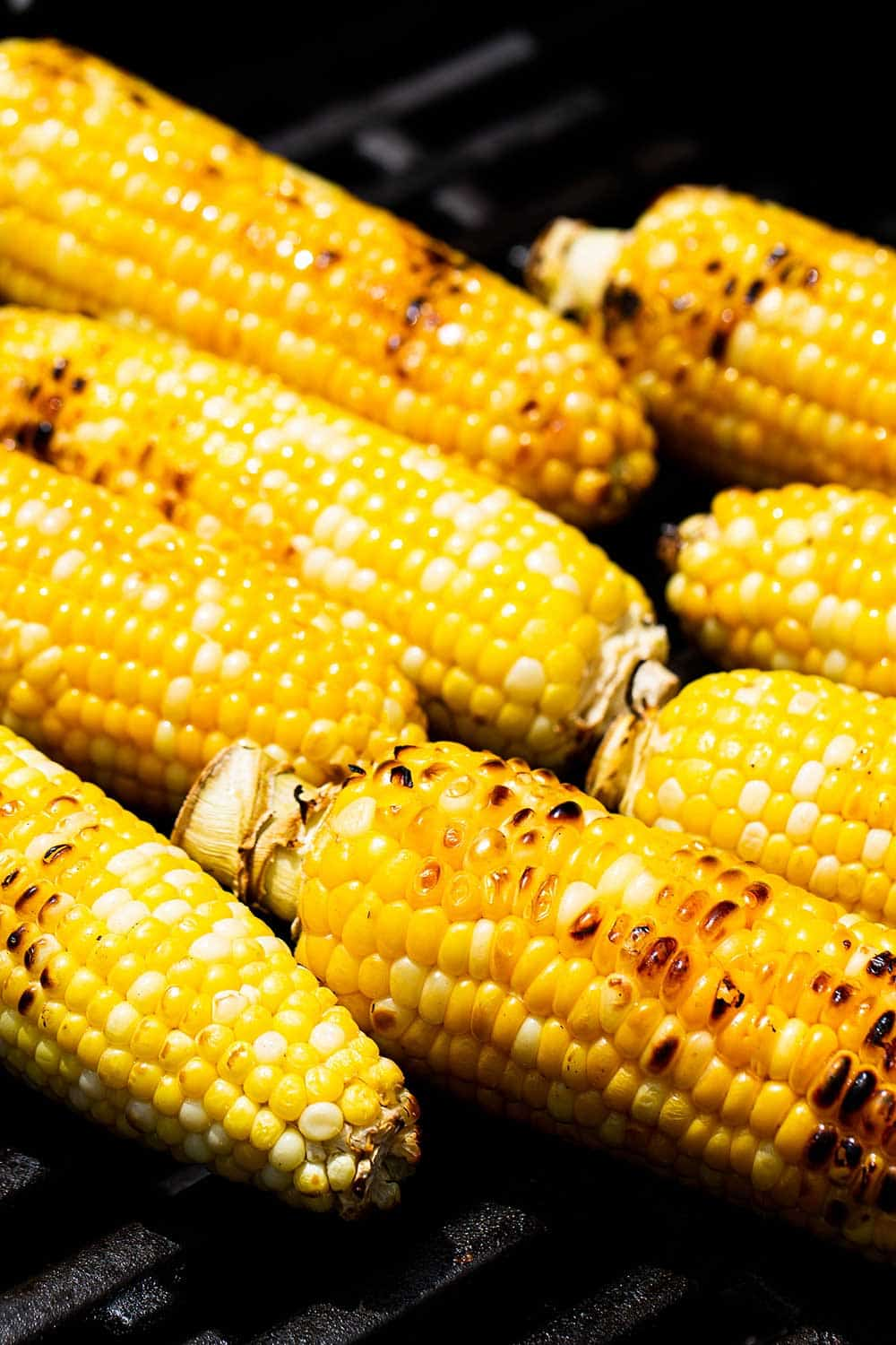 8 ears of corn being grilled on a gas grill.
