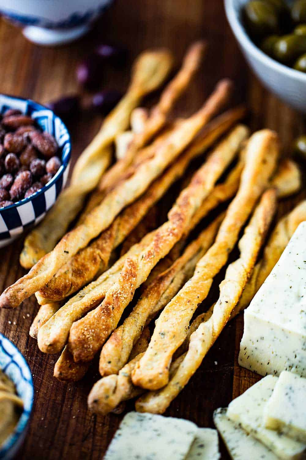 A pile of baked grissini, also known as Italian breadsticks, on a board next to a block of cheese that has been sliced and a bowl of spiced nuts.
