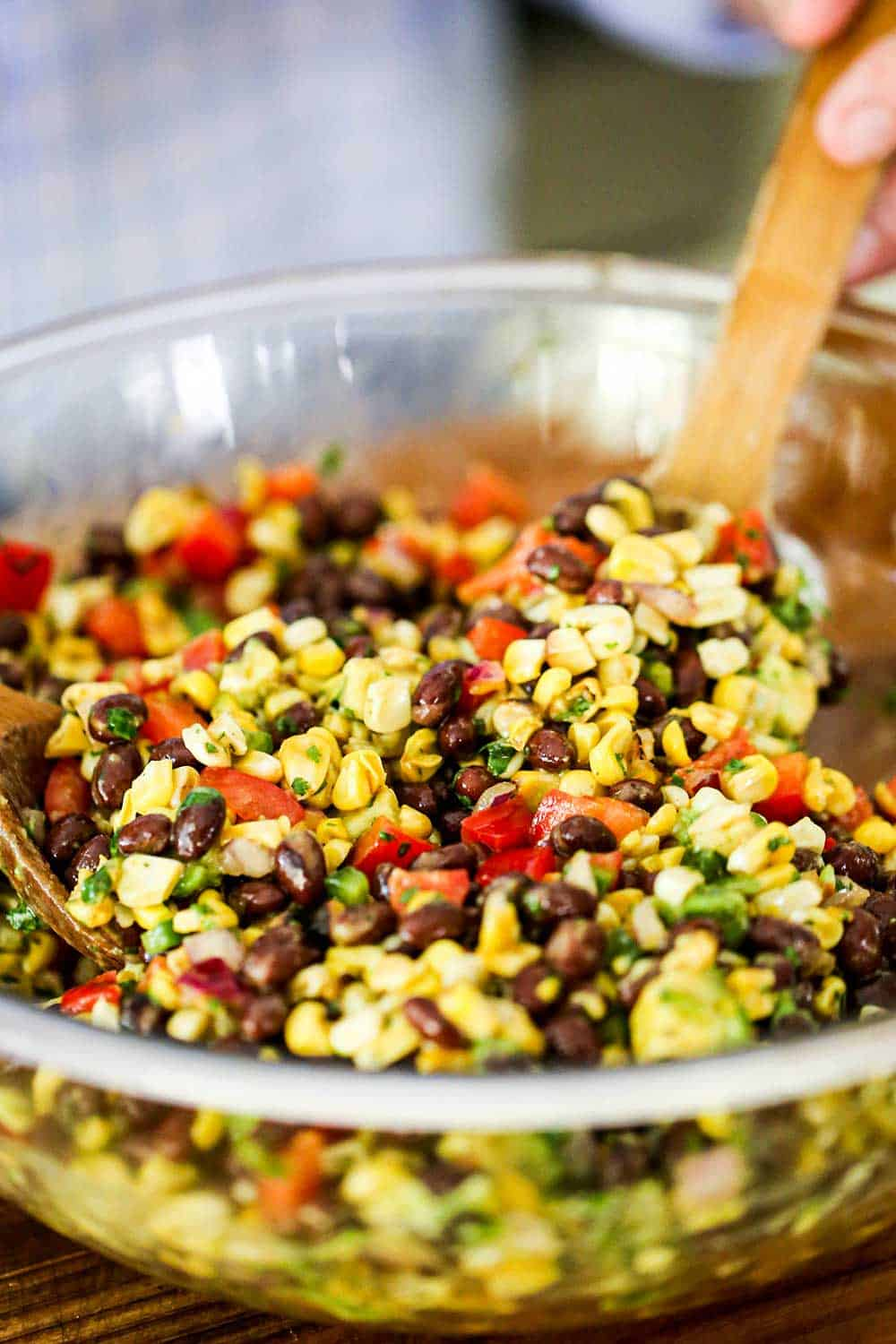 A glass bowl filled with fresh corn, black beans, red bell peppers, and avocado pieces all being stirred by a wooden spoon.