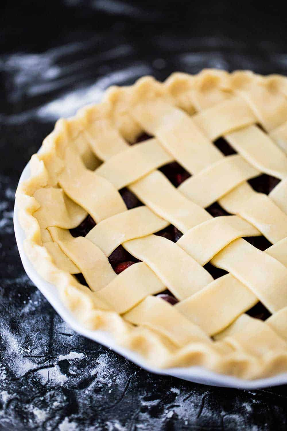 An unbaked cherry pie in a white pie dish with strips of pie dough on top in a lattice formation.