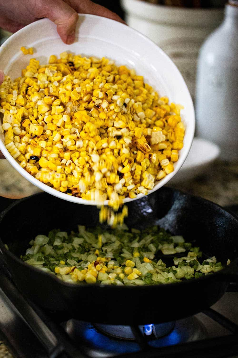 A person dumping grilled kernels of corn into a cast-iron skillet with sautéed onion and peppers in it.