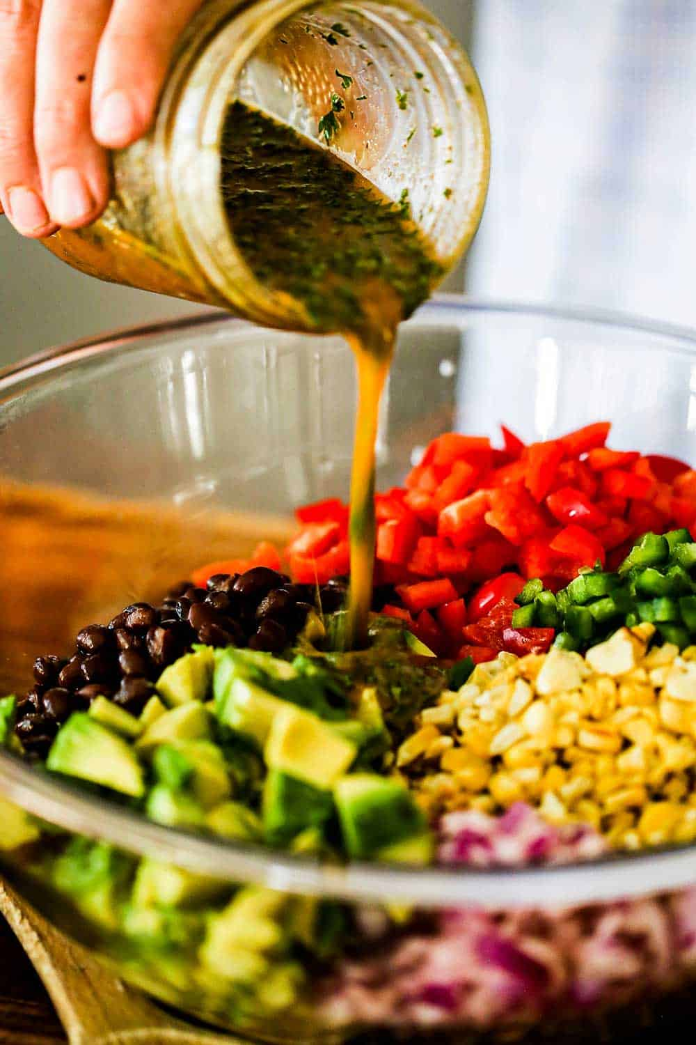 A person pouring a cilantro lime dressing from a glass jar into a glass bowl filled with black beans and cut vegetables.