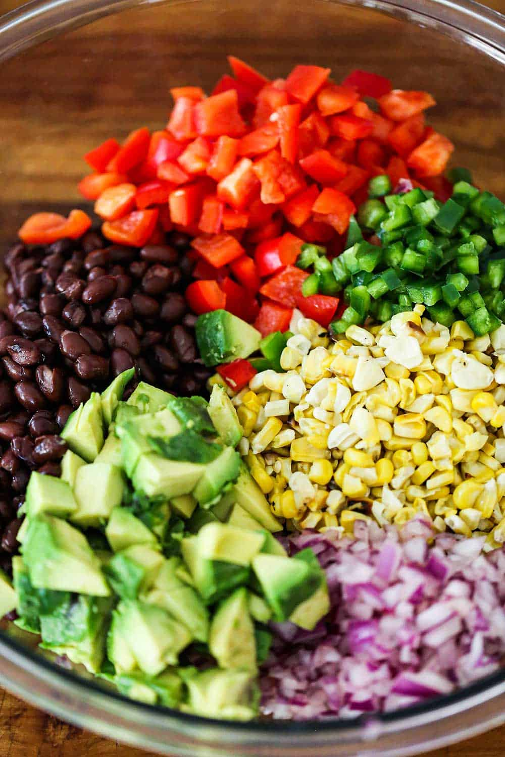 A glass bowl filled with a portion each of chopped avocado, red onion, corn kernels, jalapeno, red bell peppers, and black beans.