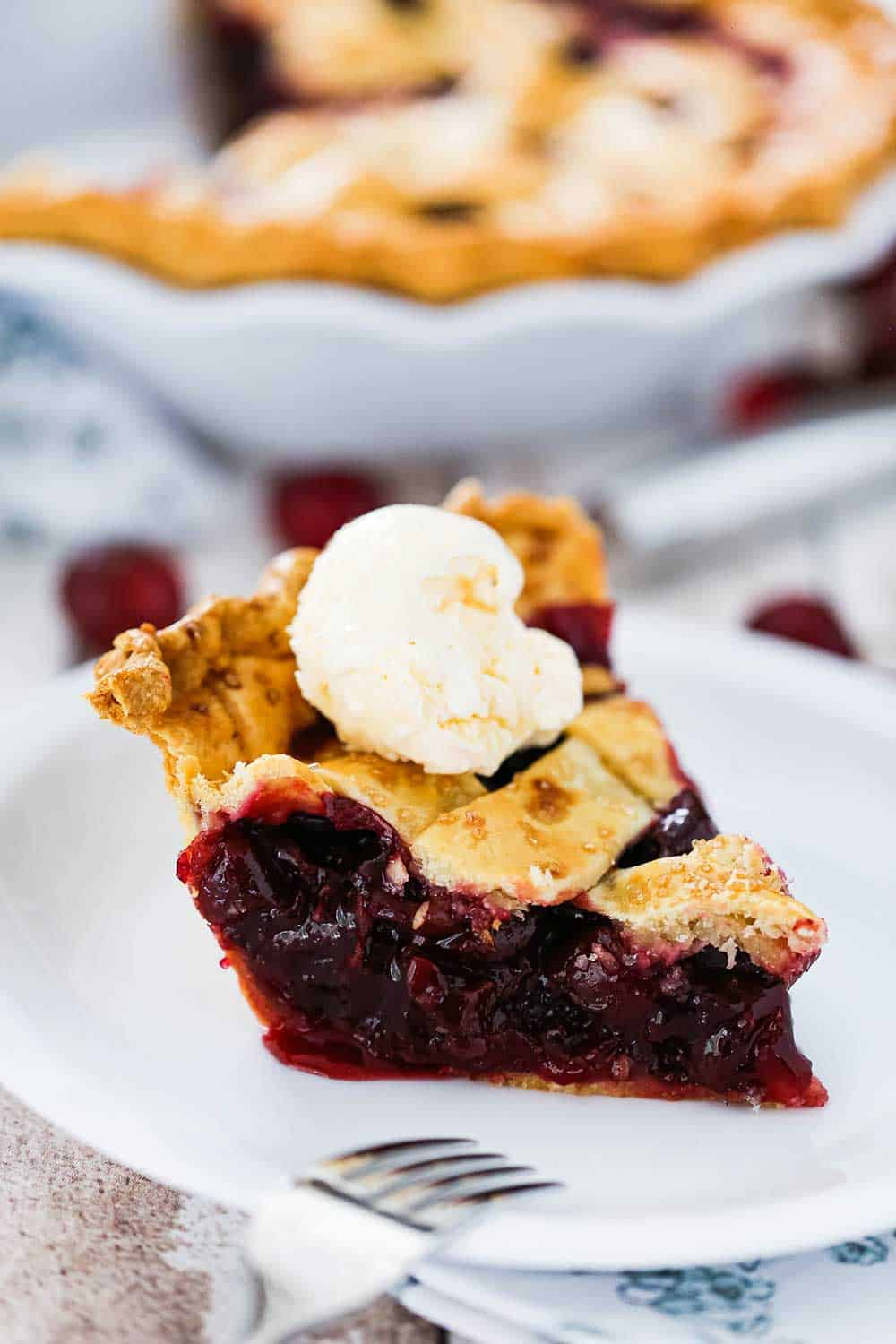 A single slice of cherry pie on a white dessert plate with a scoop of vanilla ice cream on top.