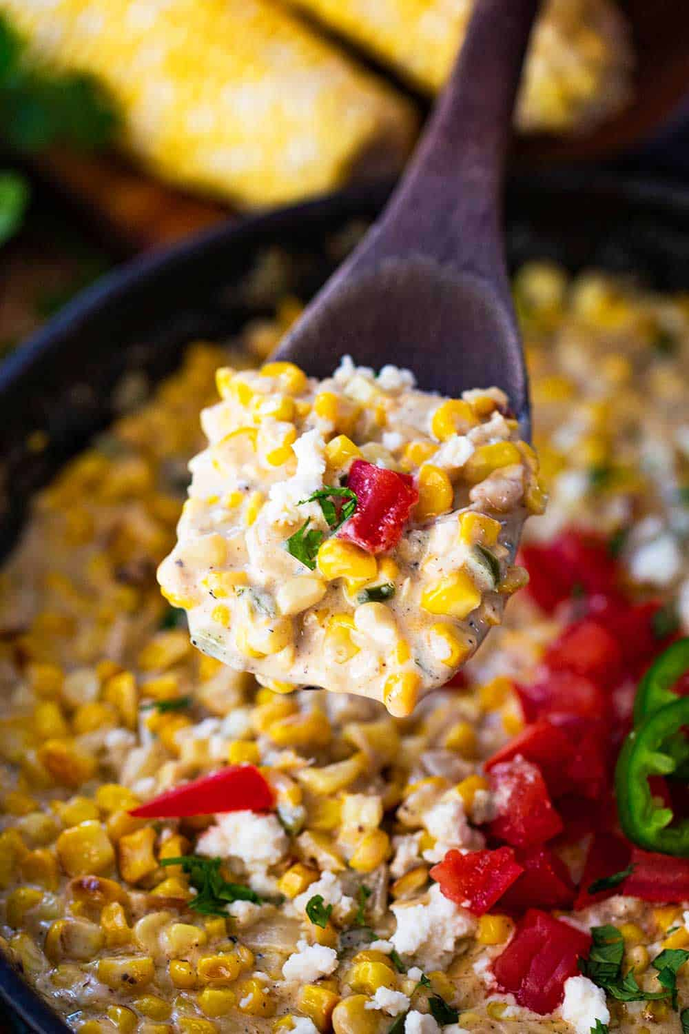 A wooden spoon lifting up a helping of Mexican cream corn from a skillet.