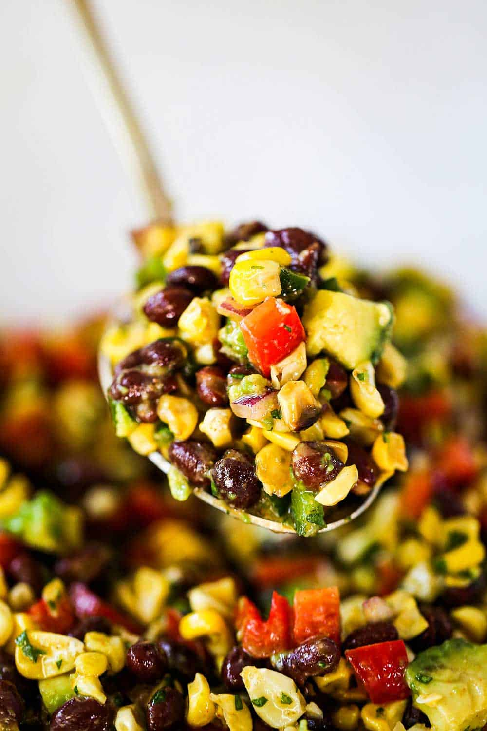 A large gold serving spoon holding up a big scoop of black bean and corn salad.