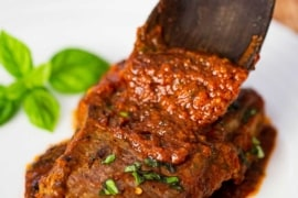 A wooden spoon transferring sauce onto steak pizzaiola on a white plate next to several basil leaves.