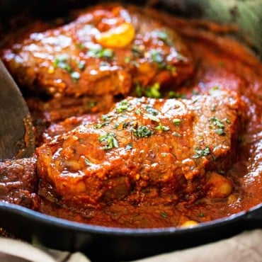 A cast-iron skillet filled with to seared steaks covered in a tomato sauce for steak pizzaiola.