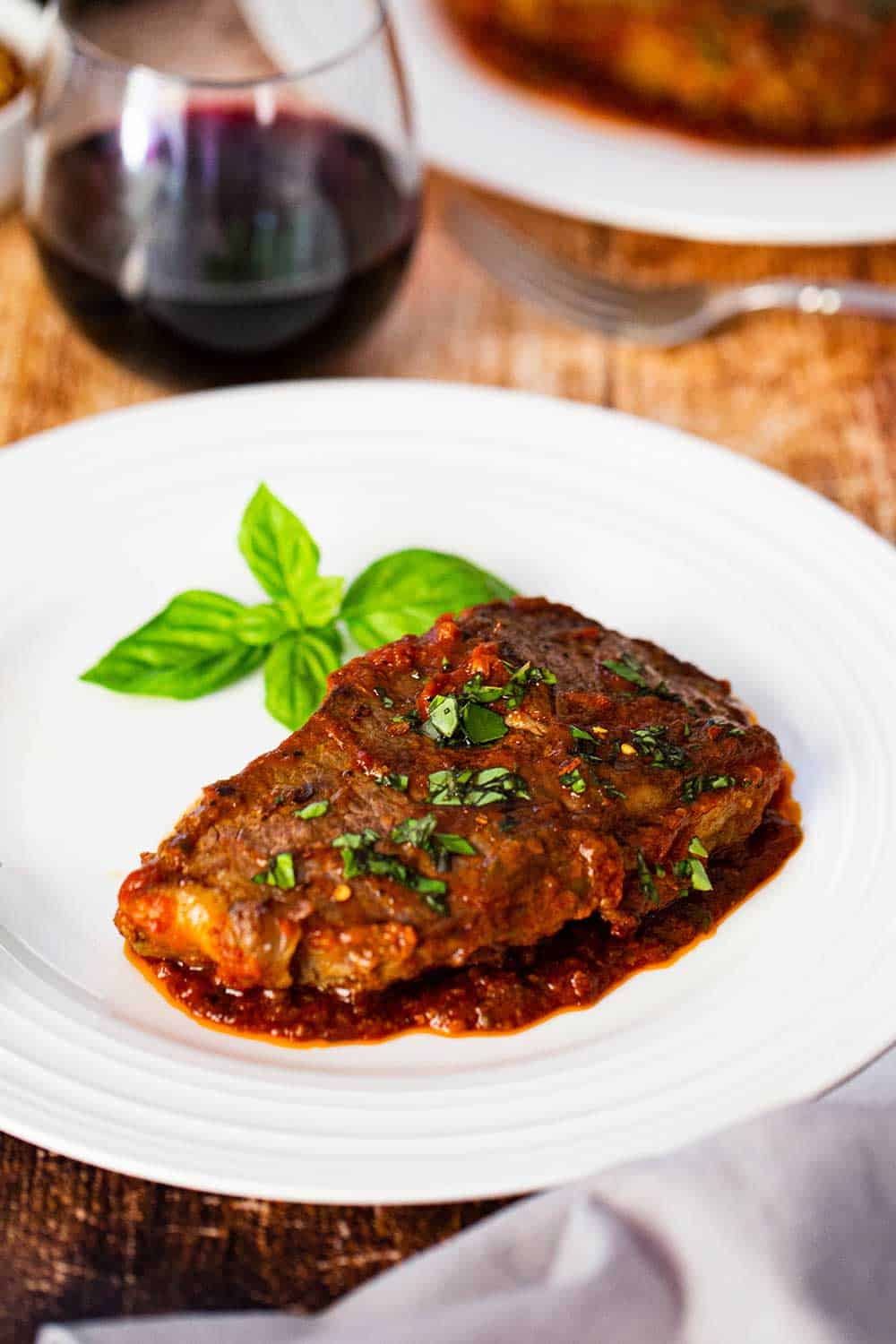 A single serving of steak pizzaiola on a white dinner plate sitting next to a glass of red wine.