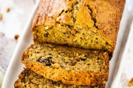 A loaf of freshly baked zucchini bread that has a couple of slices cut on an small platter.