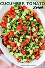 A large white oval serving dish filled with a cucumber tomato salad next to a red checkered napkin.