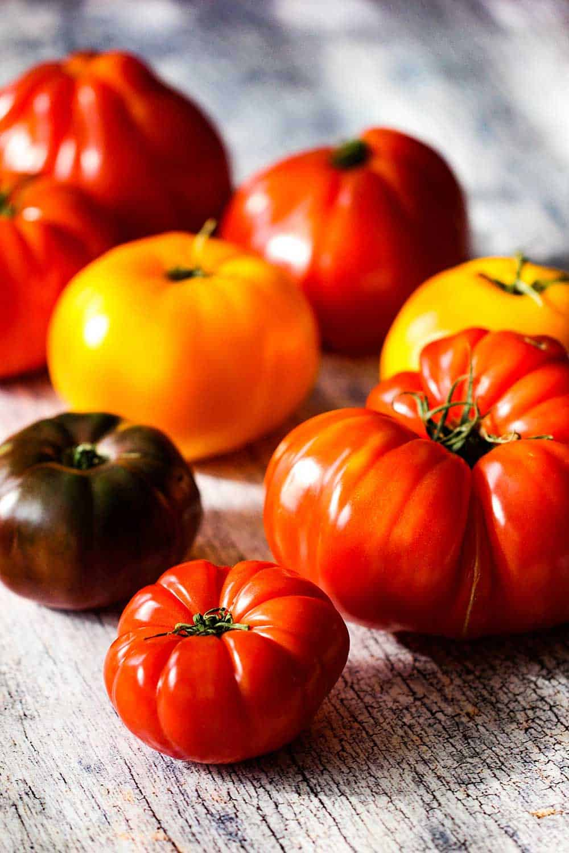 Heirloom tomatoes sitting on a wood plank
