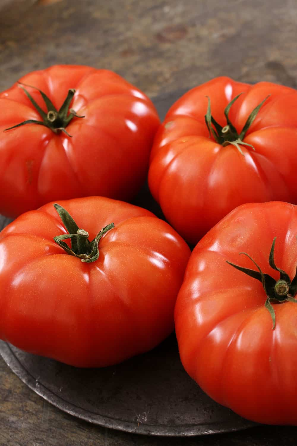Four ripe beefsteak tomatoes sitting next to each other on a brown plate.