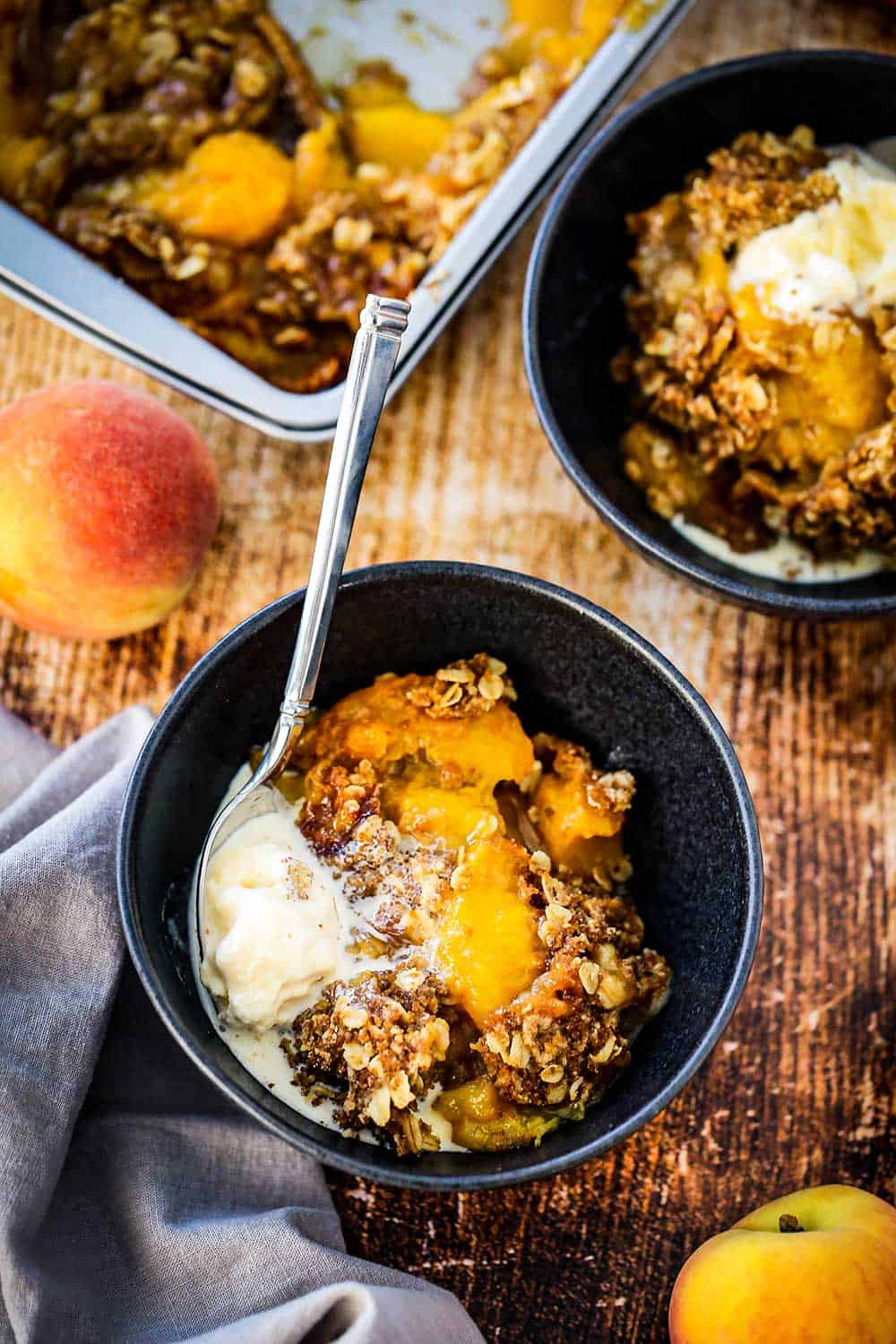 Two blue dessert bowls filled with peach crisp with a dollop of melting vanilla ice cream off to the side all next to a couple of peaches and a pan of the crisp.