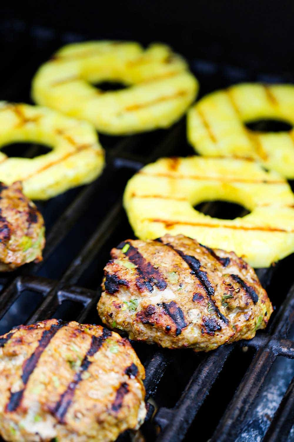 Curry turkey burgers on a gas grill next to 4 slices of fresh pineapple all with grill marks on their surfaces.