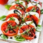 A white rectangular platter holding layers of slice tomatoes and mozzarella to form a caprese salad being topped with squirts of pesto sauce from a squeeze bottle.