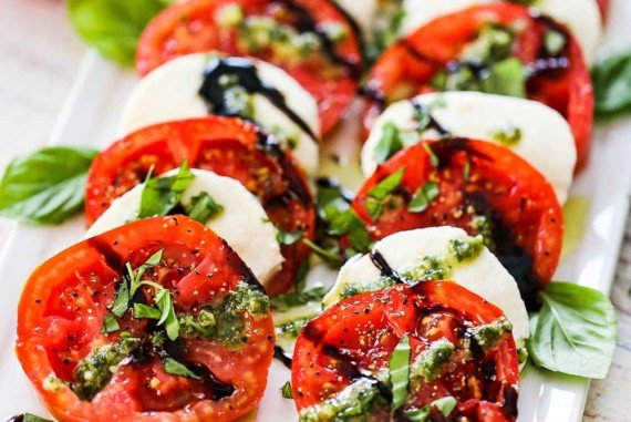 A platter of caprese salad that has been drizzled with pesto sauce and a balsamic glaze and topped with freshly chopped basil.