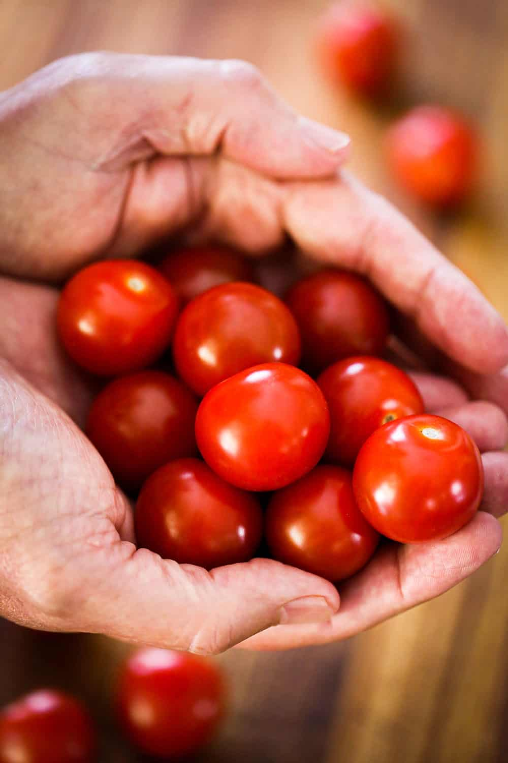 Two hands holding a bunch of ripe cherry tomatoes.