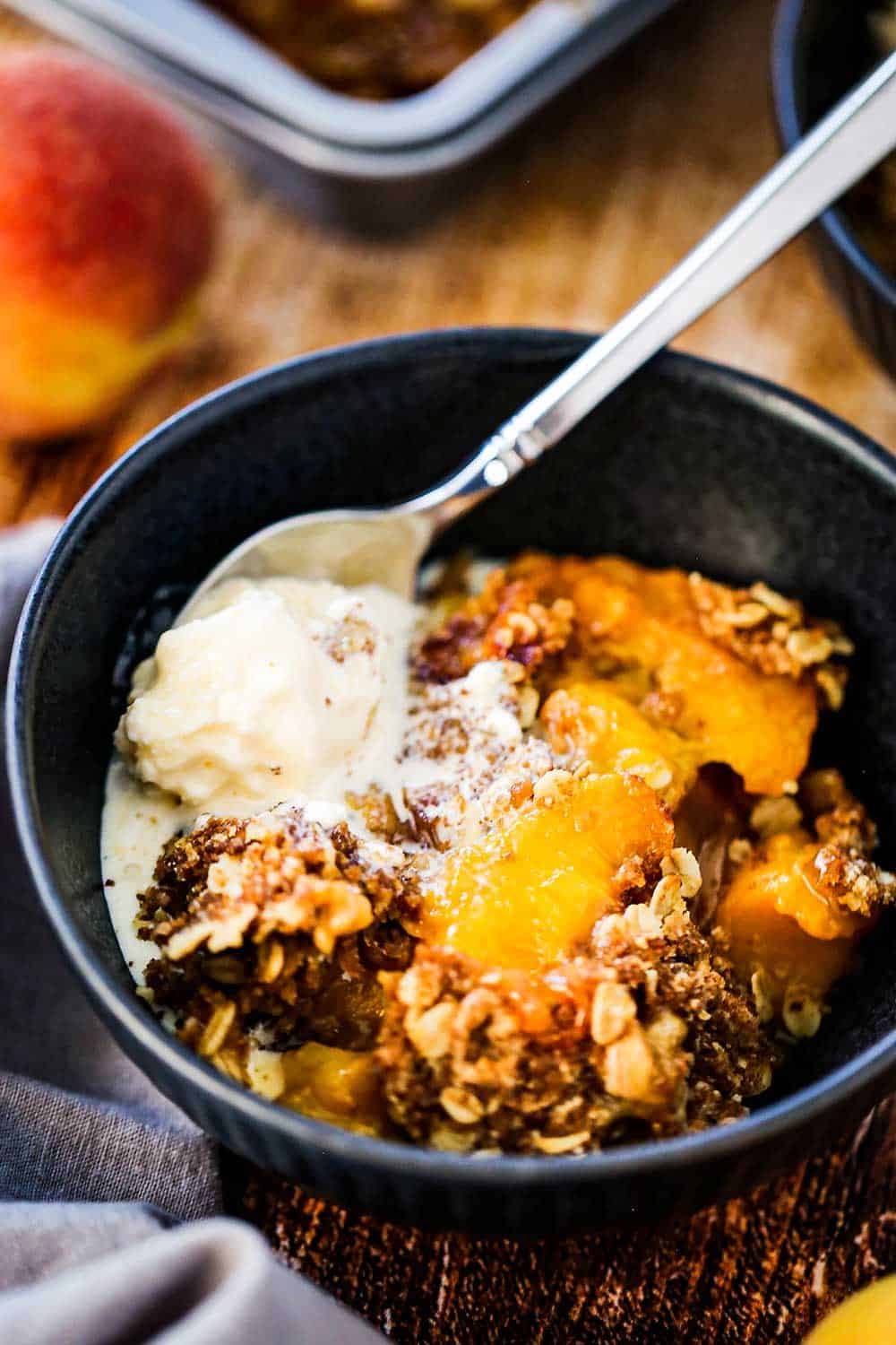 A blue dessert bowl filled with a helping of peach crisp with a scoop of melting vanilla ice cream on top.