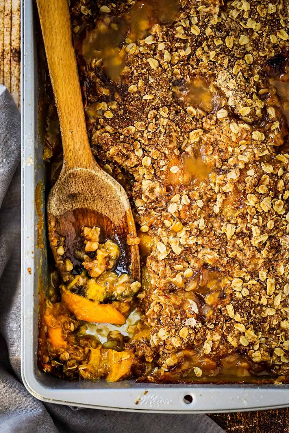 A silver baking pan filled with fully baked peach crisp with a wooden spoon inserted in the side.