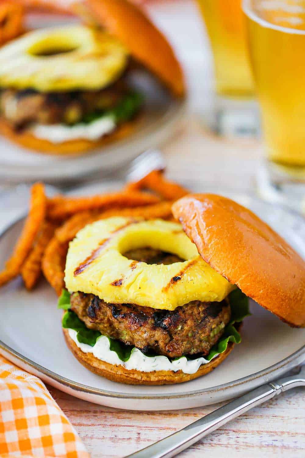 A curry turkey burger with grilled pineapple sitting on a plate next to sweet potato crinkle fries with a couple glasses of beer in the background.