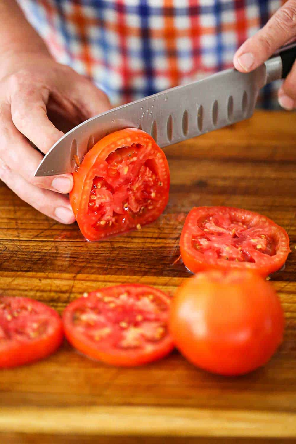 A person using a chef's knife to slice a very red tomato on a cutting board with other tomato slices nearby.