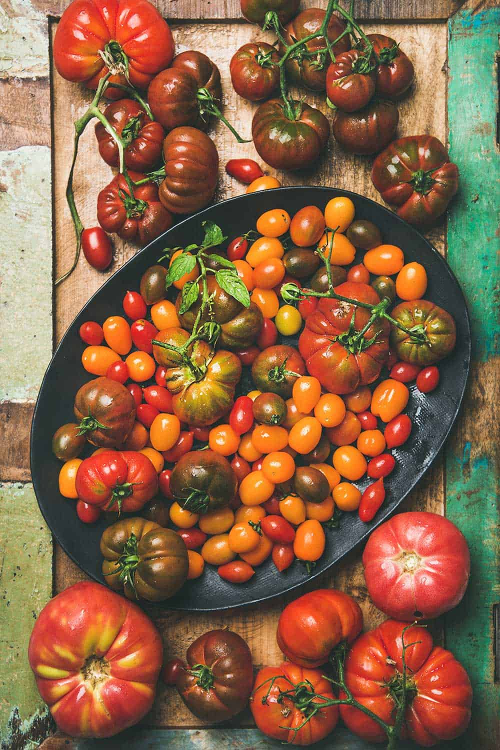 A bowl filled with and surrounded by a large variety of types of tomatoes including cherry, beefsteak, heirloom, and roma.