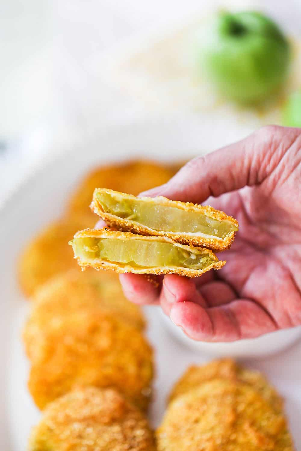 A hand holding up a fried green tomato that has been in half so the inside of the tomato is visible.