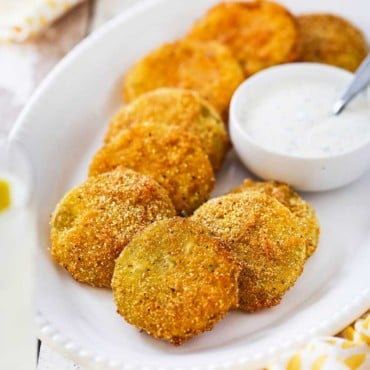 An oval white platter filled with fried green tomatoes with a small bowl of ranch dressing sitting next to them.