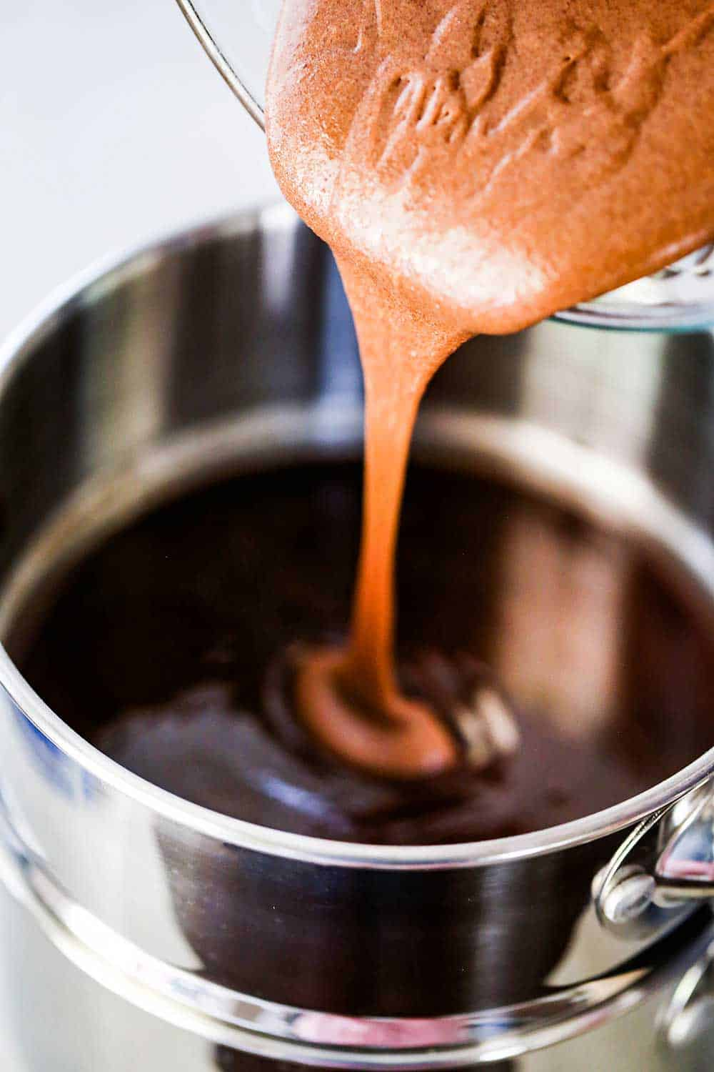 A creamy chocolate mixture being transferred from a glass bowl into a double boiler filled with melted butter and chocolate.