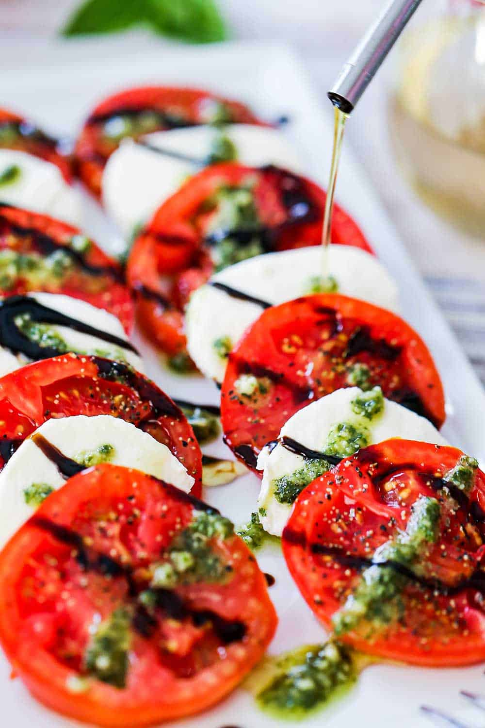 A thin drizzle of olive oil being poured from an olive oil dispenser onto a platter filled with caprese salad.
