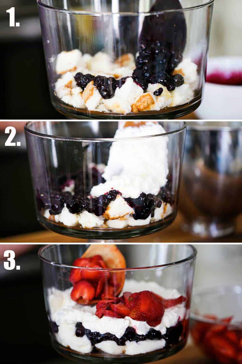 A spoon layering a blueberry sauce over pieces of angel food cake in a trifle dish, and then cream being spooned over the blueberries, and then strawberries being added.